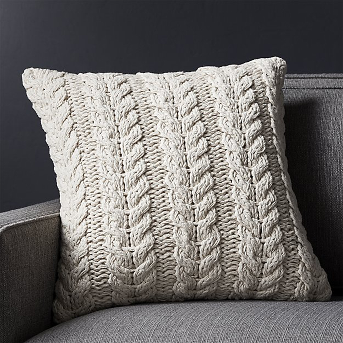 Decorative cable-knit pillow in a neutral hue photo