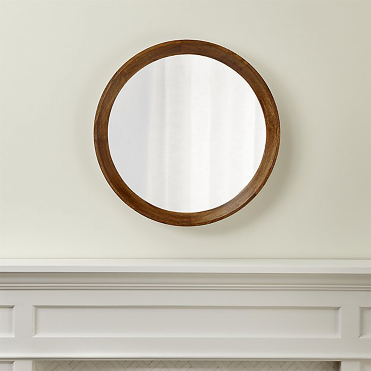 Circular mirror made of mango wood from Crate and Barrel hanging above a mantle. photo