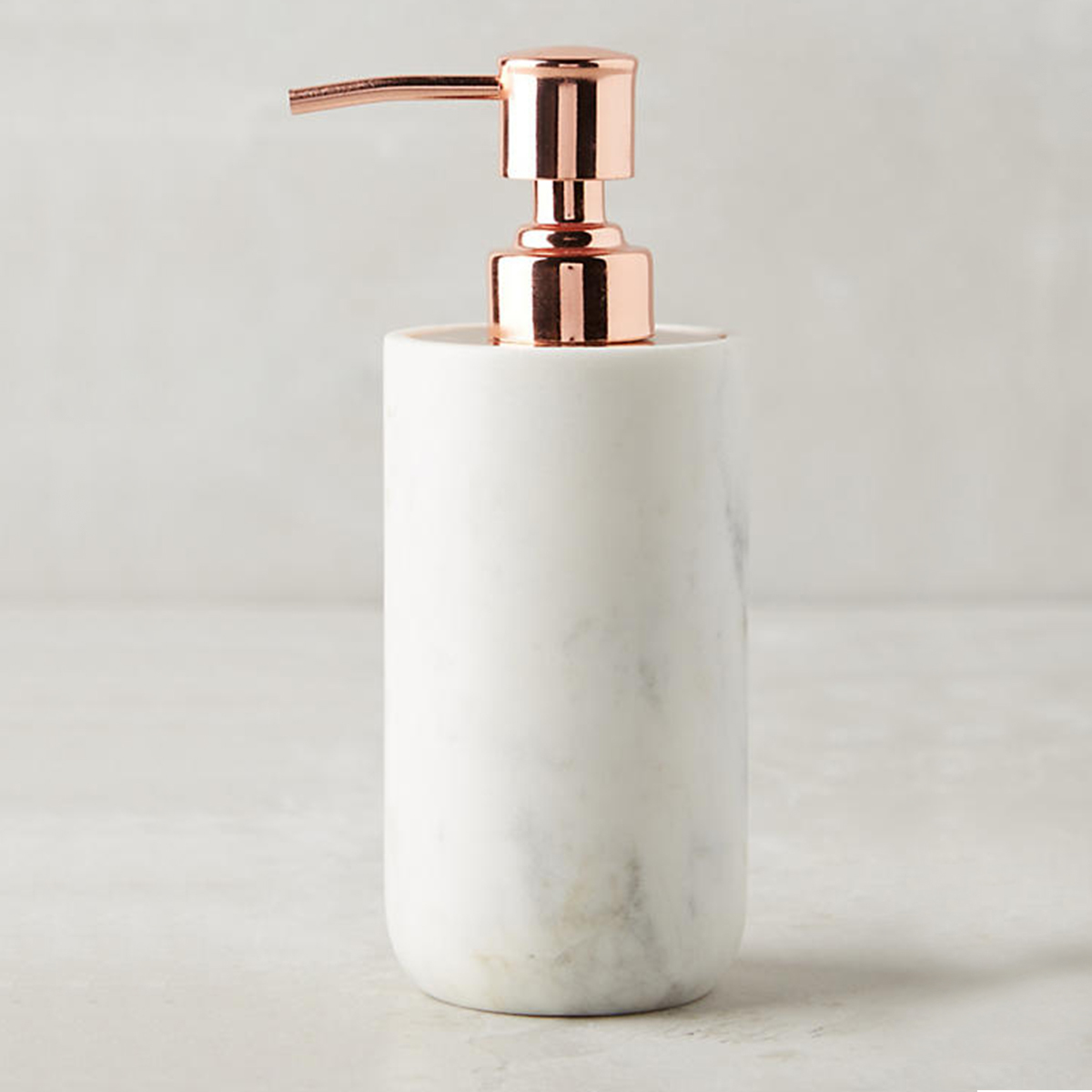 White marble soap dispenser with a rose gold pump from Anthropologie photo