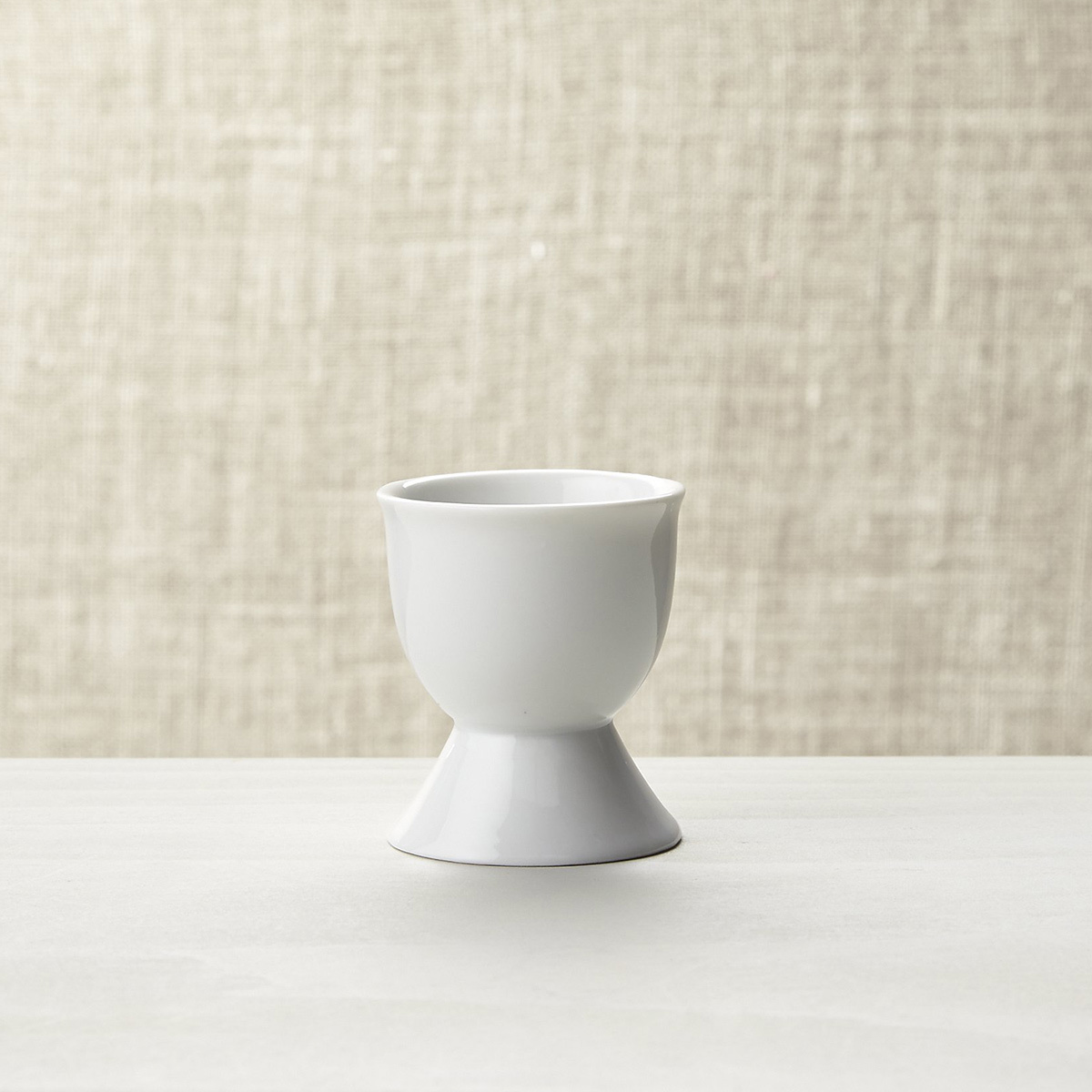 Small white egg cup that fits one egg photo
