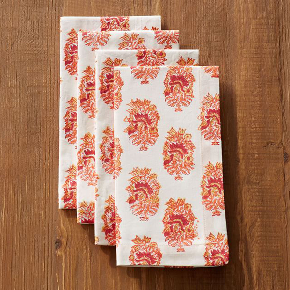 White cloth napkins with a red, orange and pink print on them photo