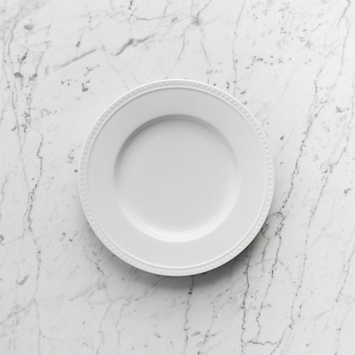 White dinnerware with a dotted rim. photo