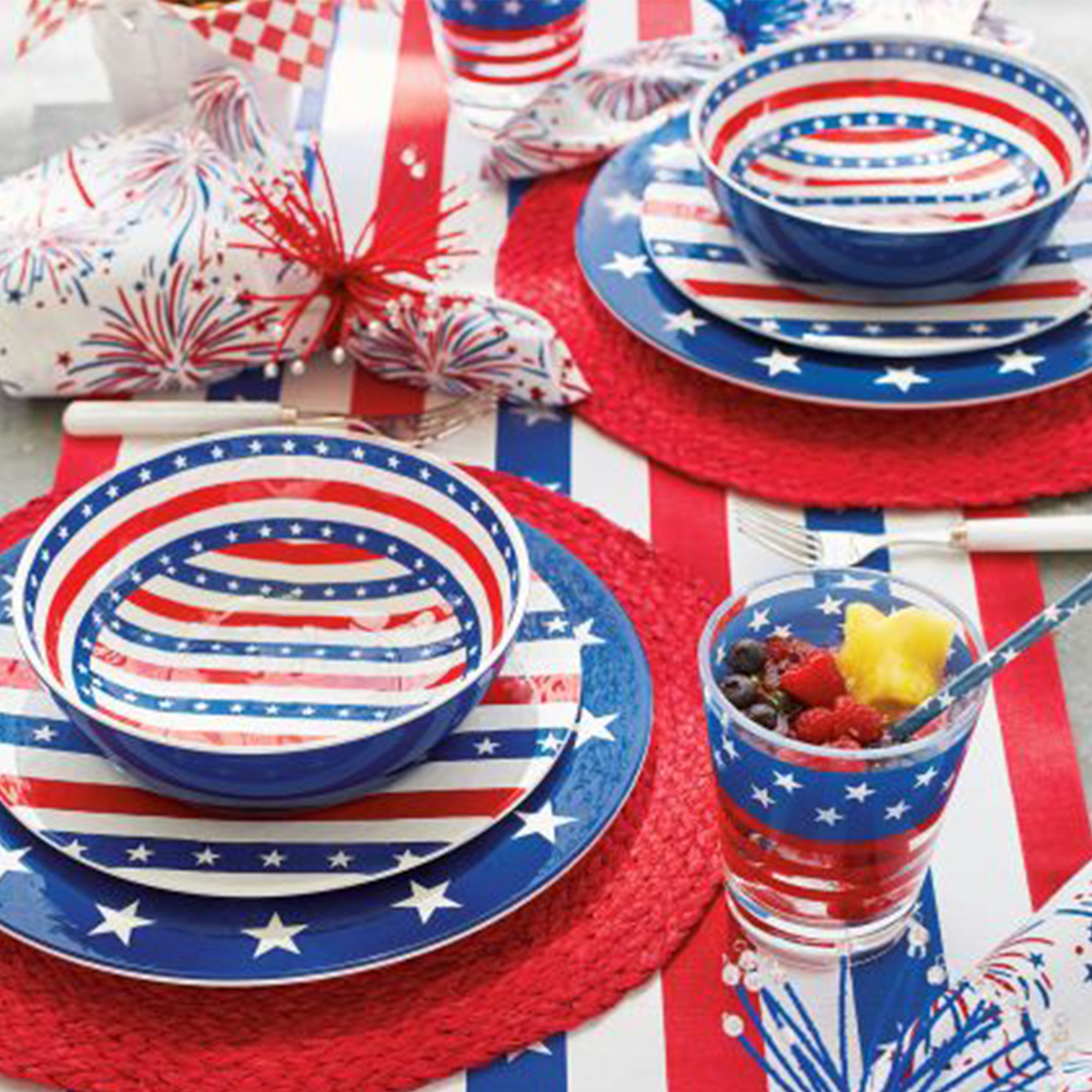 Red, white, and blue dinnerware set with striped patterns on the bowls, plates, and cups photo