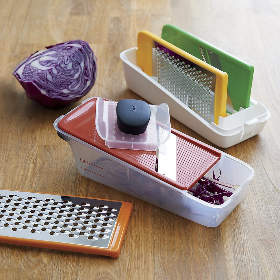 A meal prep set including grating and slicing blaes, a holding container, and an organizer photo