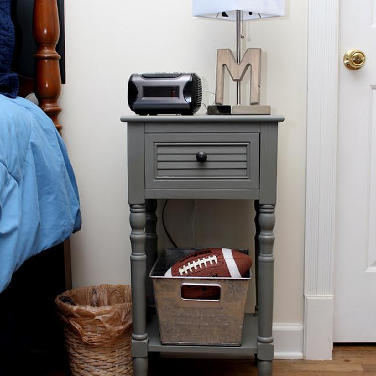 Gray side table with storage basket and lamp on top photo