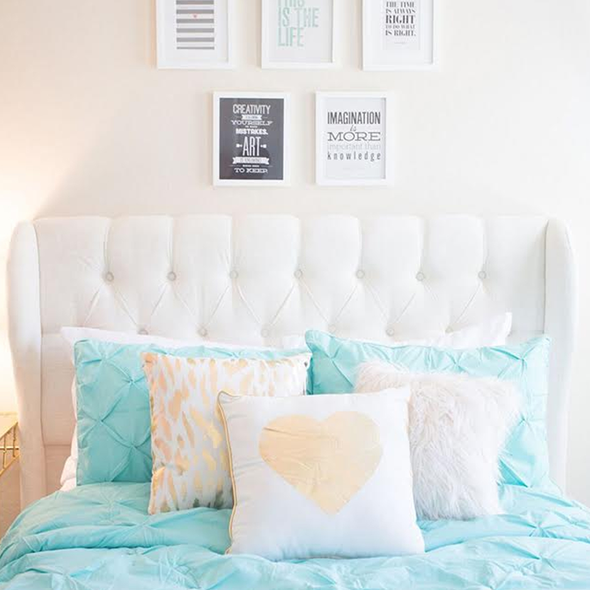 Coastal styled room with white tufted headboard and bright turquoise bedding photo