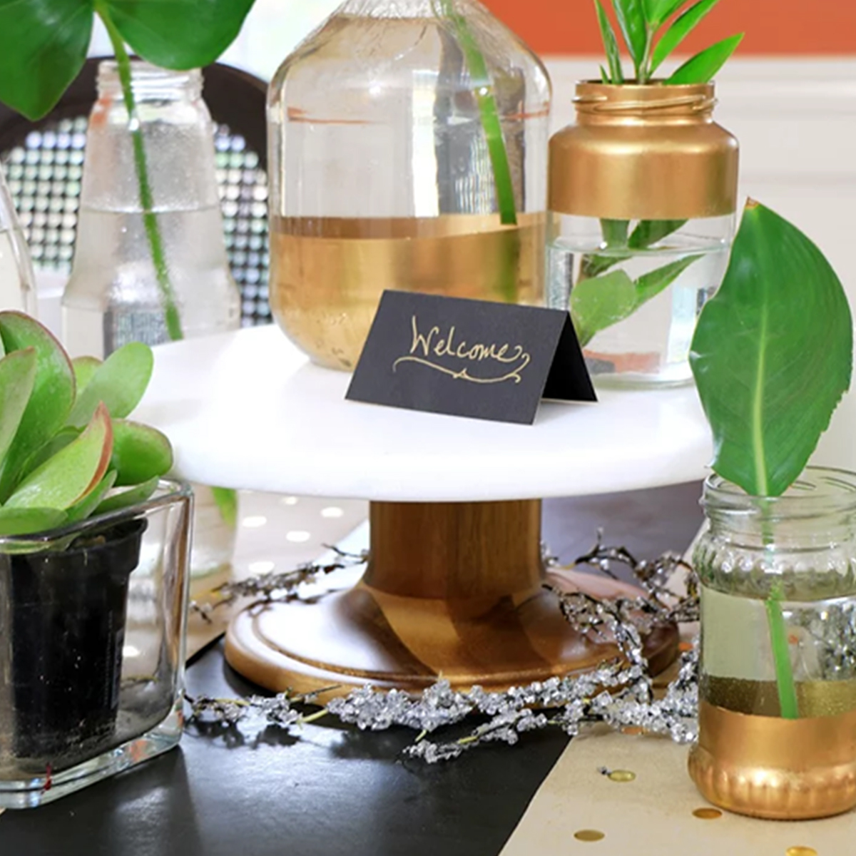 Better Homes & Gardens cake stand with gold vases next to it photo