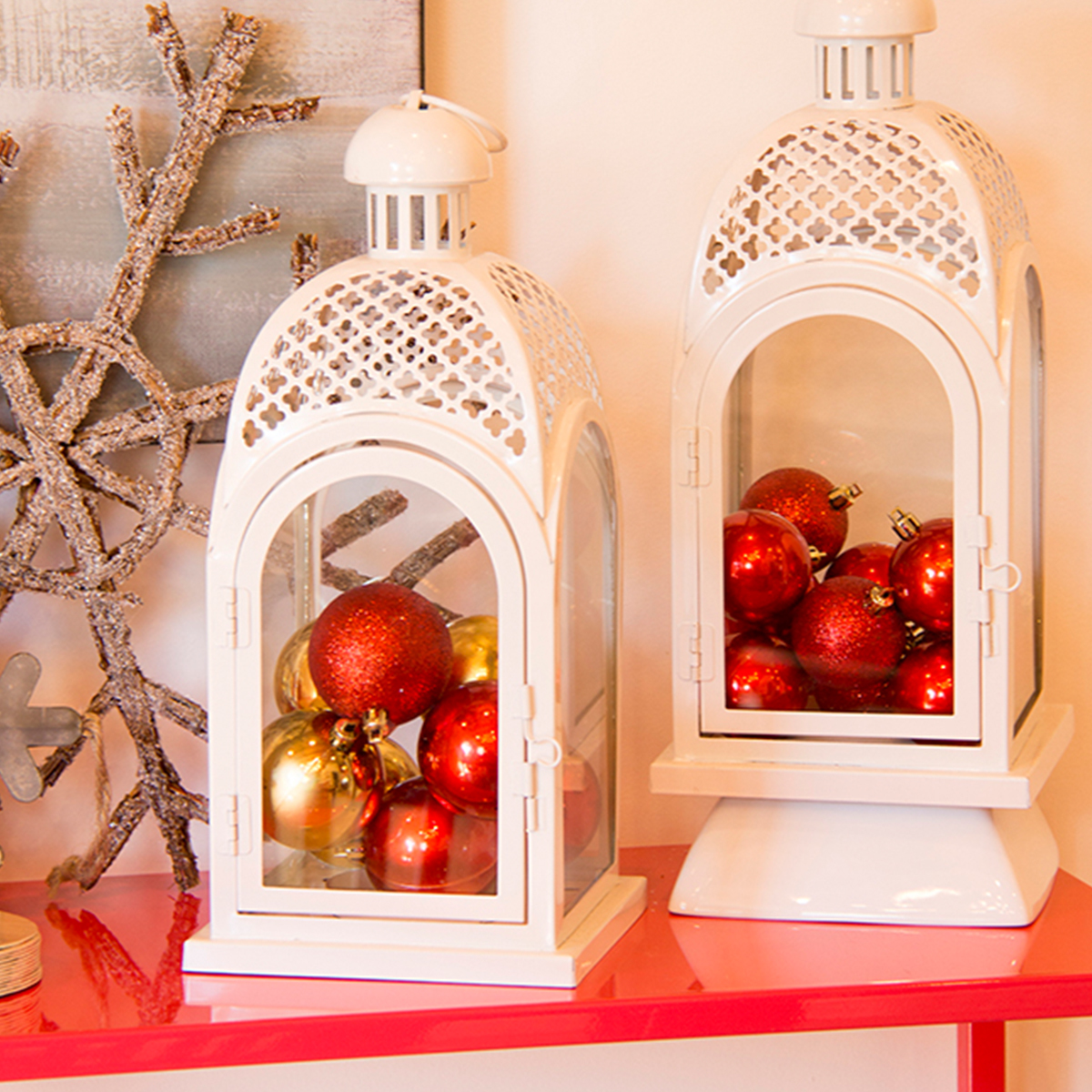 Better Homes & Gardens white lanterns with red and gold Christmas ornaments in them photo