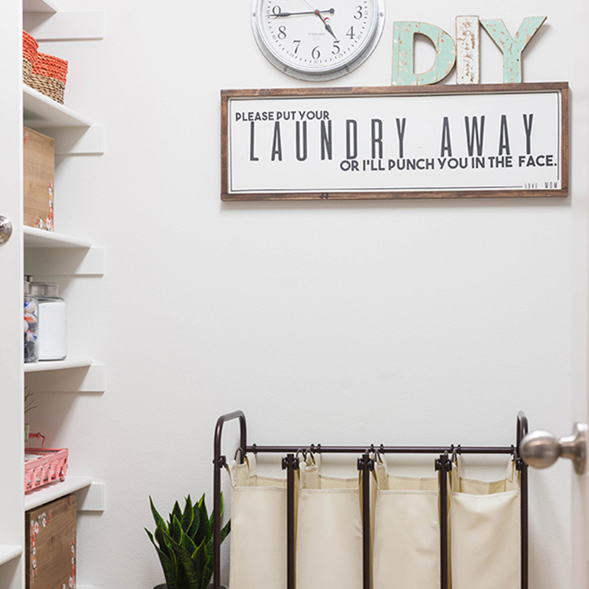 Organized laundry room featuring galvanized metal clock and laundry sorter. photo