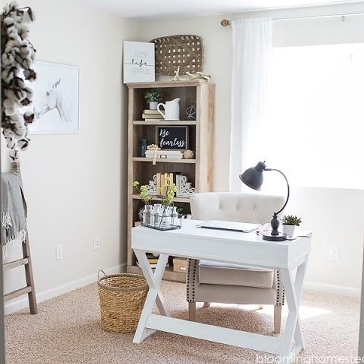 Home office with white wood desk, gray desk lamp, and wooden bookshelf photo