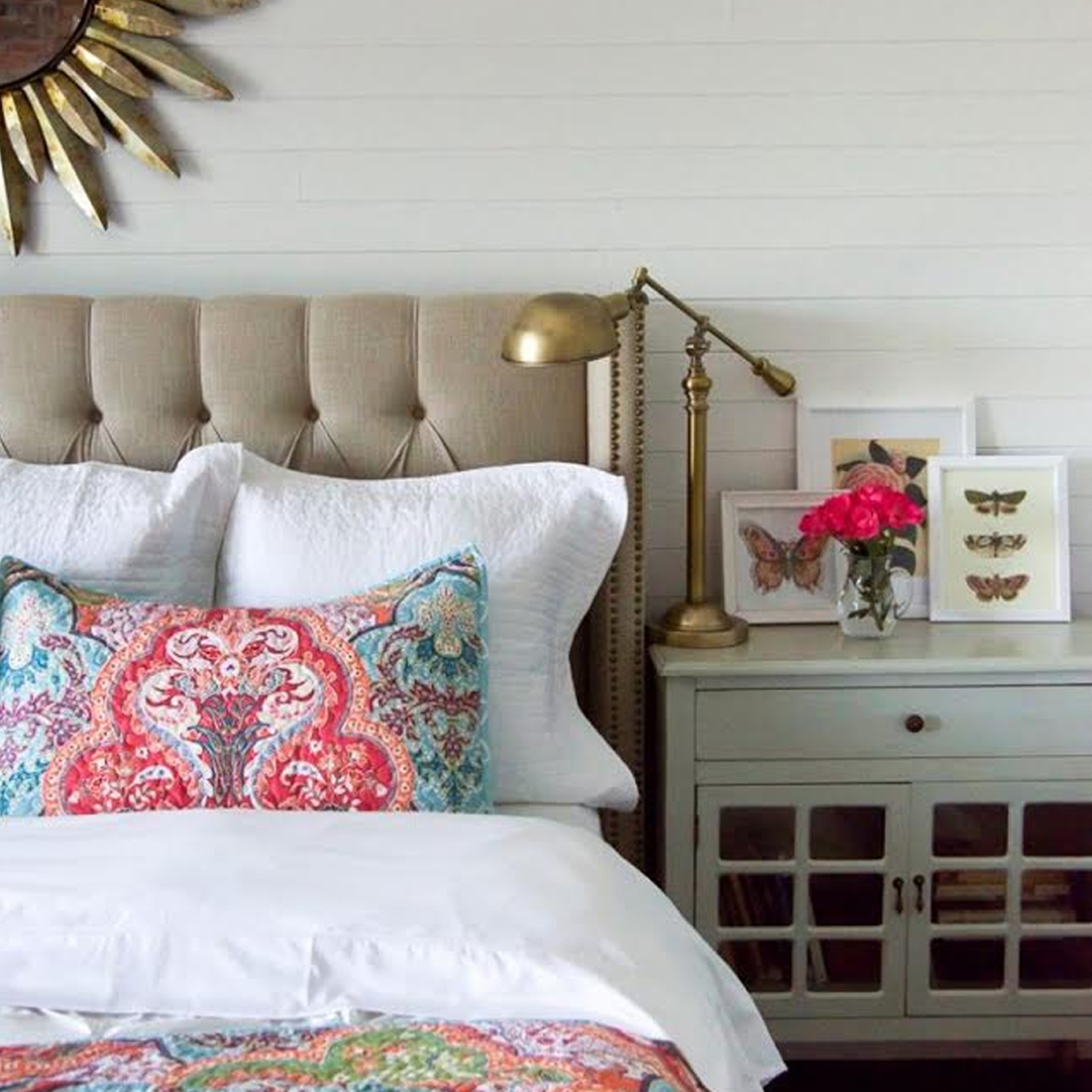 Bed with fabric headboard, white blankets, and colorful pillows photo