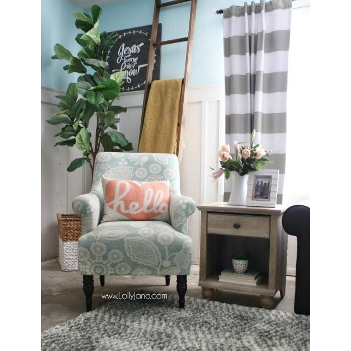 Upholstered accent chair next to wooden side table with drawer photo
