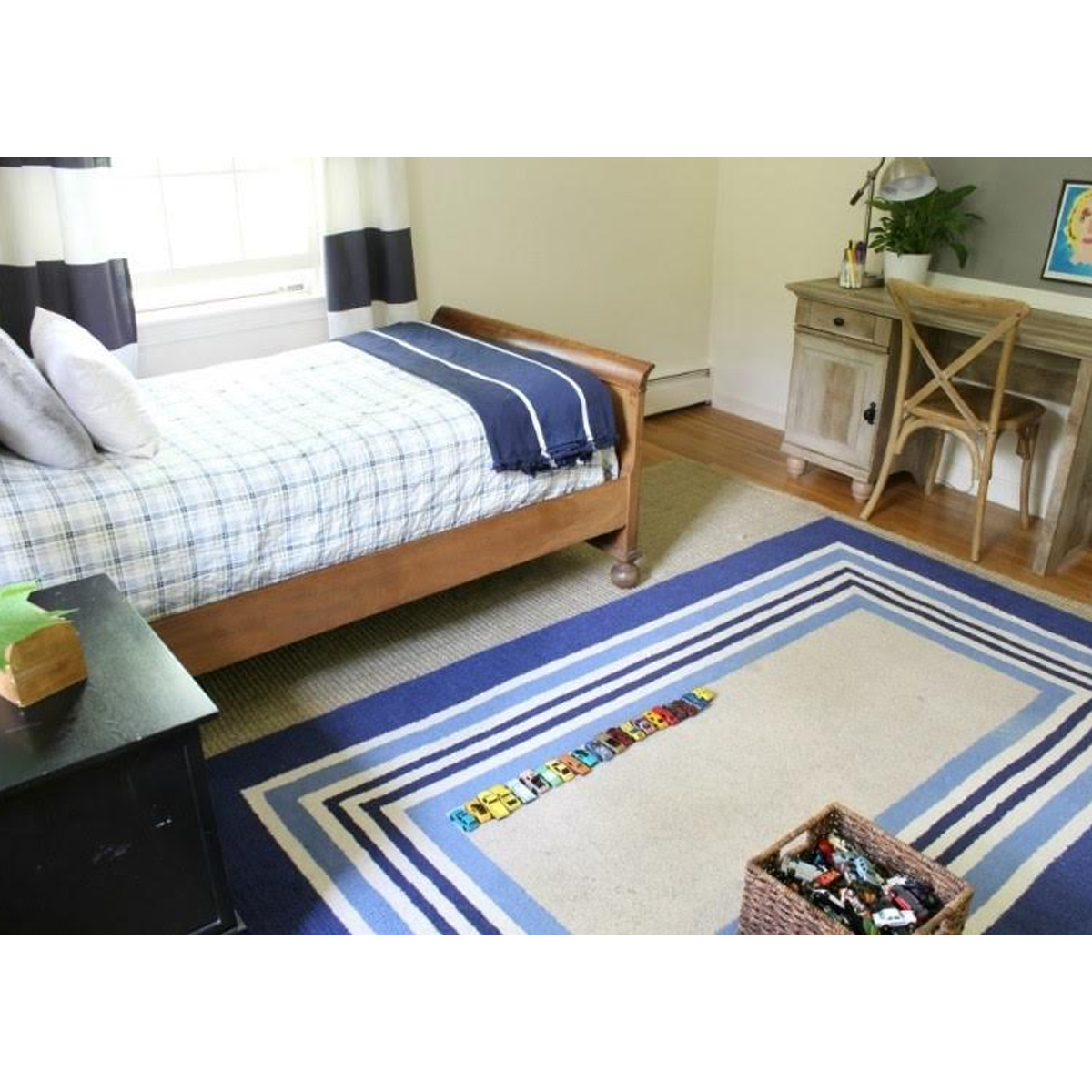 Boys bedroom with blue striped rug, wooden bed frame, and blue checker bedding photo