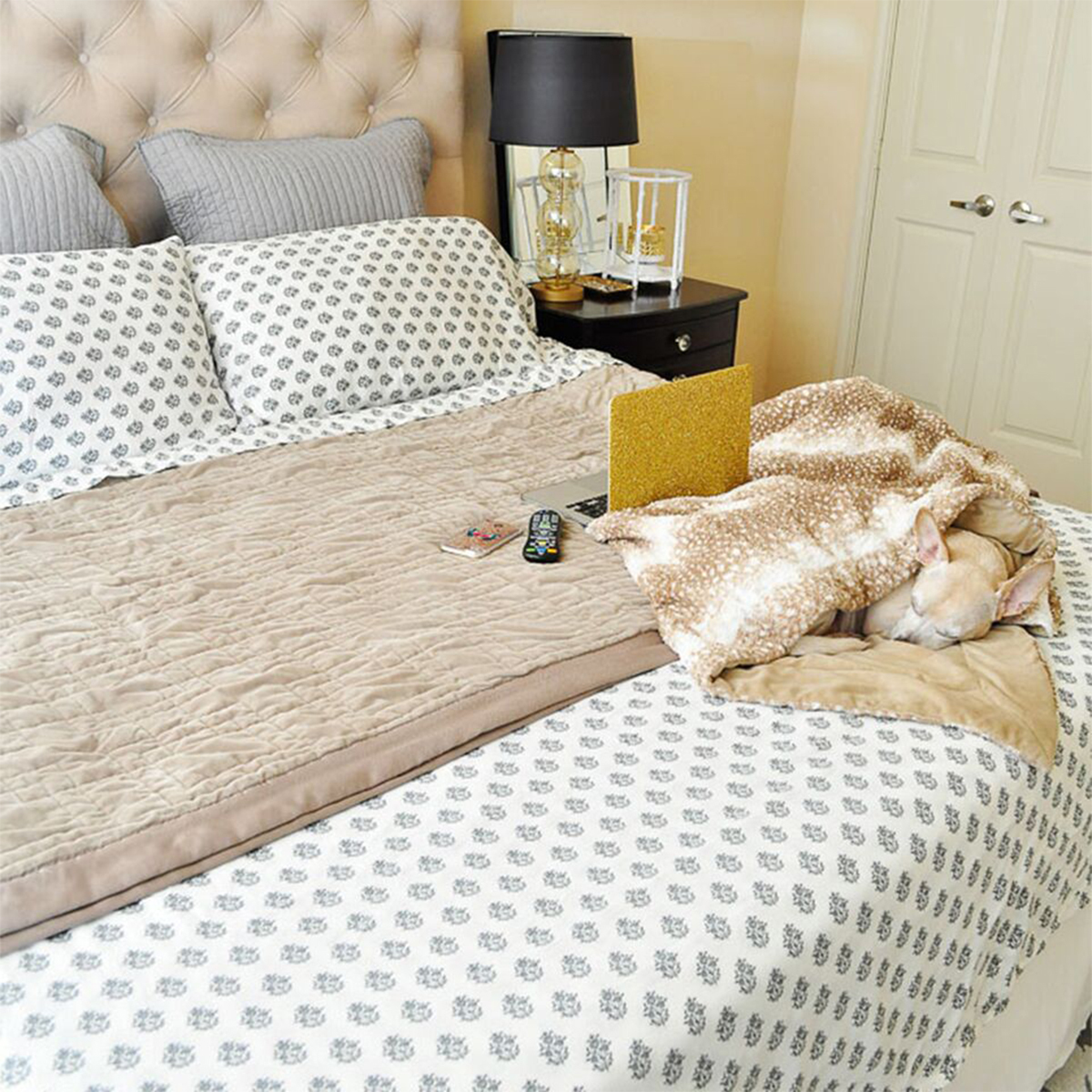 Bed with patterned comfortoer, gold blanket, and matching pillows photo