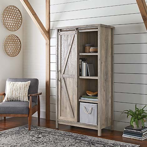 The Rustic Gray finish gives off total farm vibes, and behind the sliding barn door sits 5 adjustable shelves, just waiting to hold your favorite towels, books, and other possessions. photo