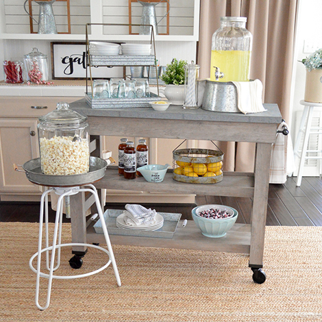 Fun snack bar created with farmhouse multi-purpose cart, adjustable spin stool, beverage dispenser, and porcelain dinnerware. photo