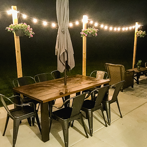 Enjoy warm summer nights with Edison string lights and camrose farmhouse industrial chairs for a relaxed atmosphere. photo