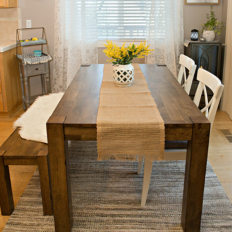 Bryant dining table paired with the Bryant dining bench and two white chairs. photo