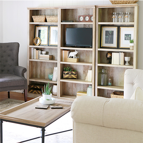 Crossmill 5-shelf bookcase and river crest coffee table are two pieces to give any space a farmhouse feel. photo