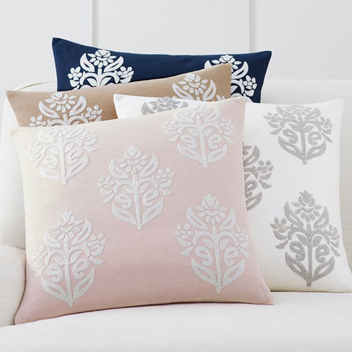 Plush pillows with an embroidered floral print in four colors. photo