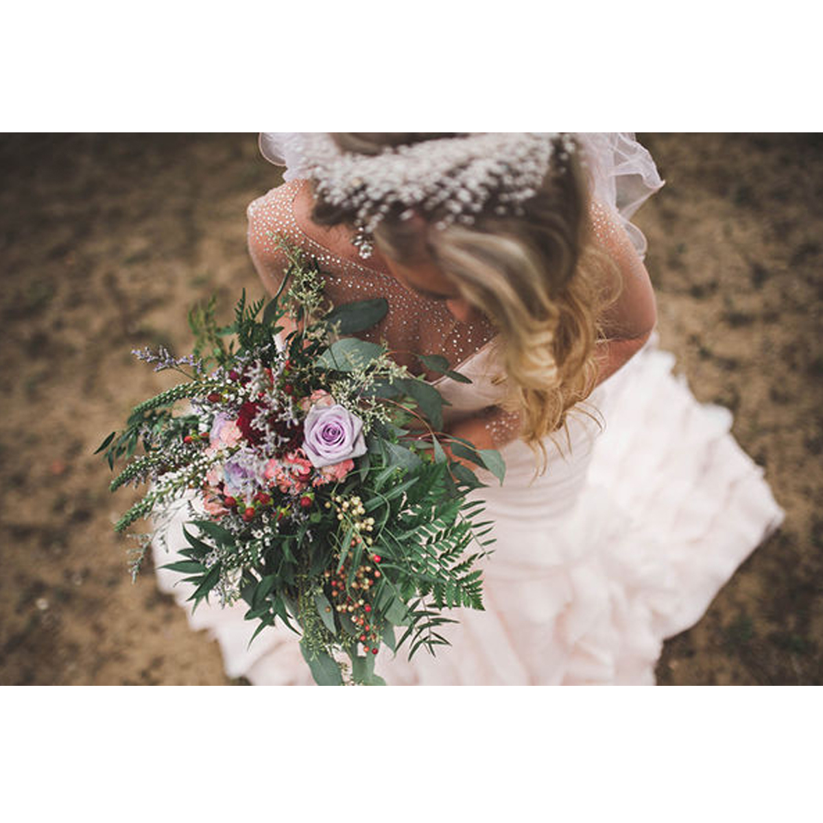 Bride in a white gown and veil holding a green boquet with a few pink flowers photo