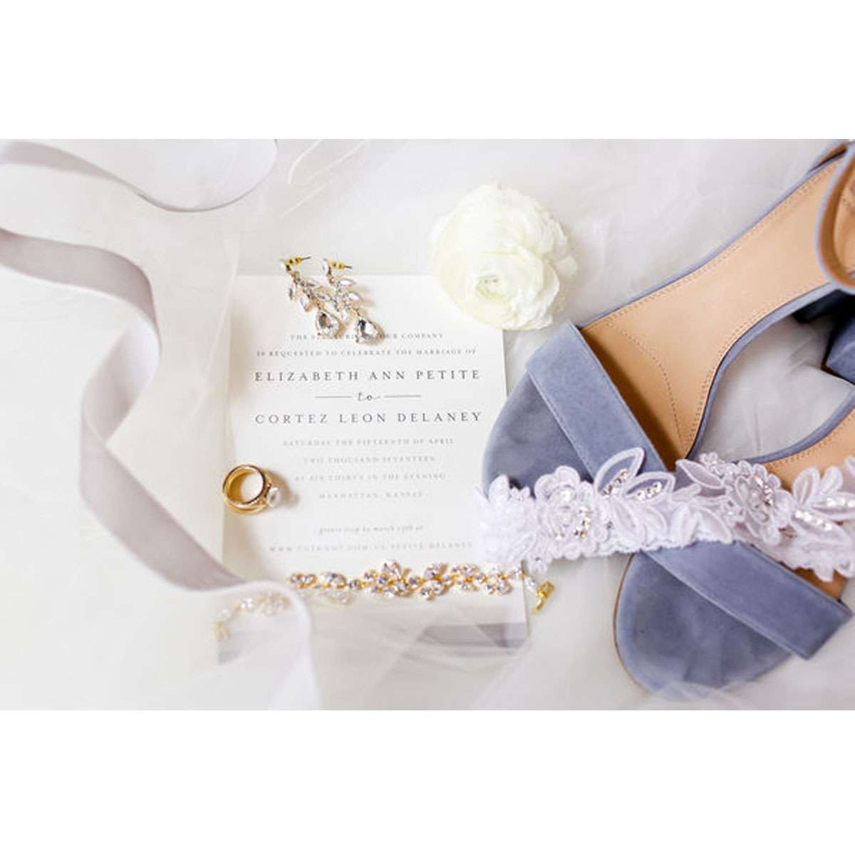 Light blue heels next to a wedding invitation, wedding ring, and ribbons photo