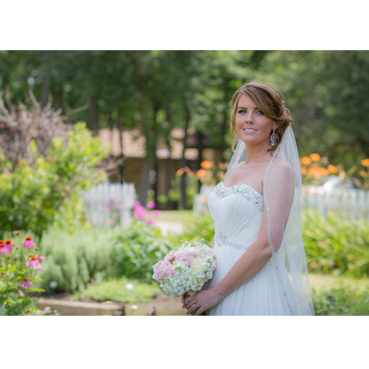 Bride in a white dress and veil poses in a garden with a pink and green boquet photo