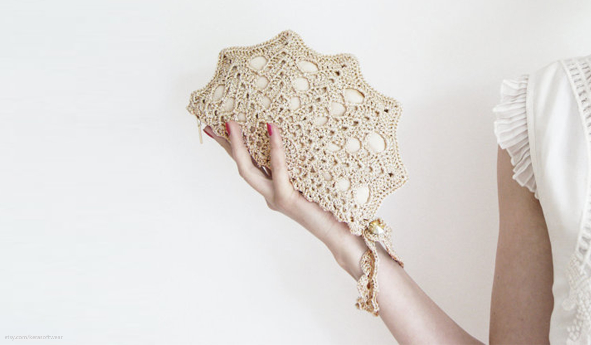 Model holds scalloped-edged lacey clutch