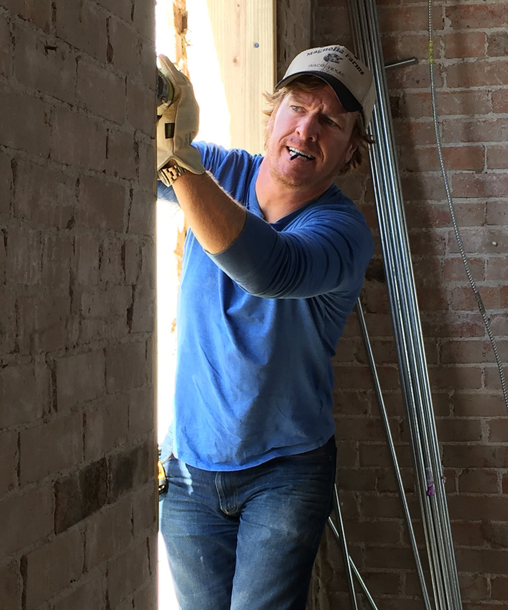 Chip Gaines working on a brick wall photo