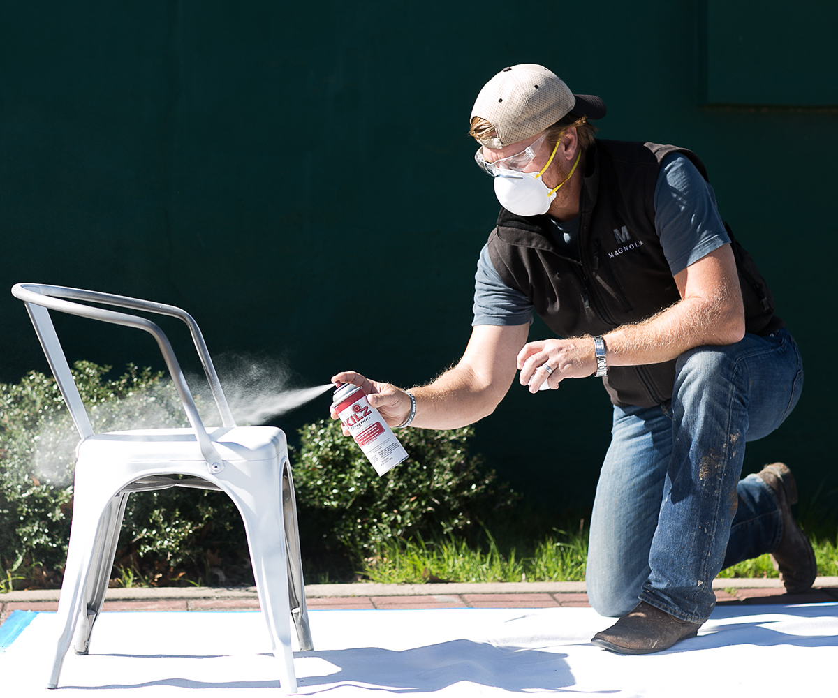 Chip Gaines spray painting a chair white photo