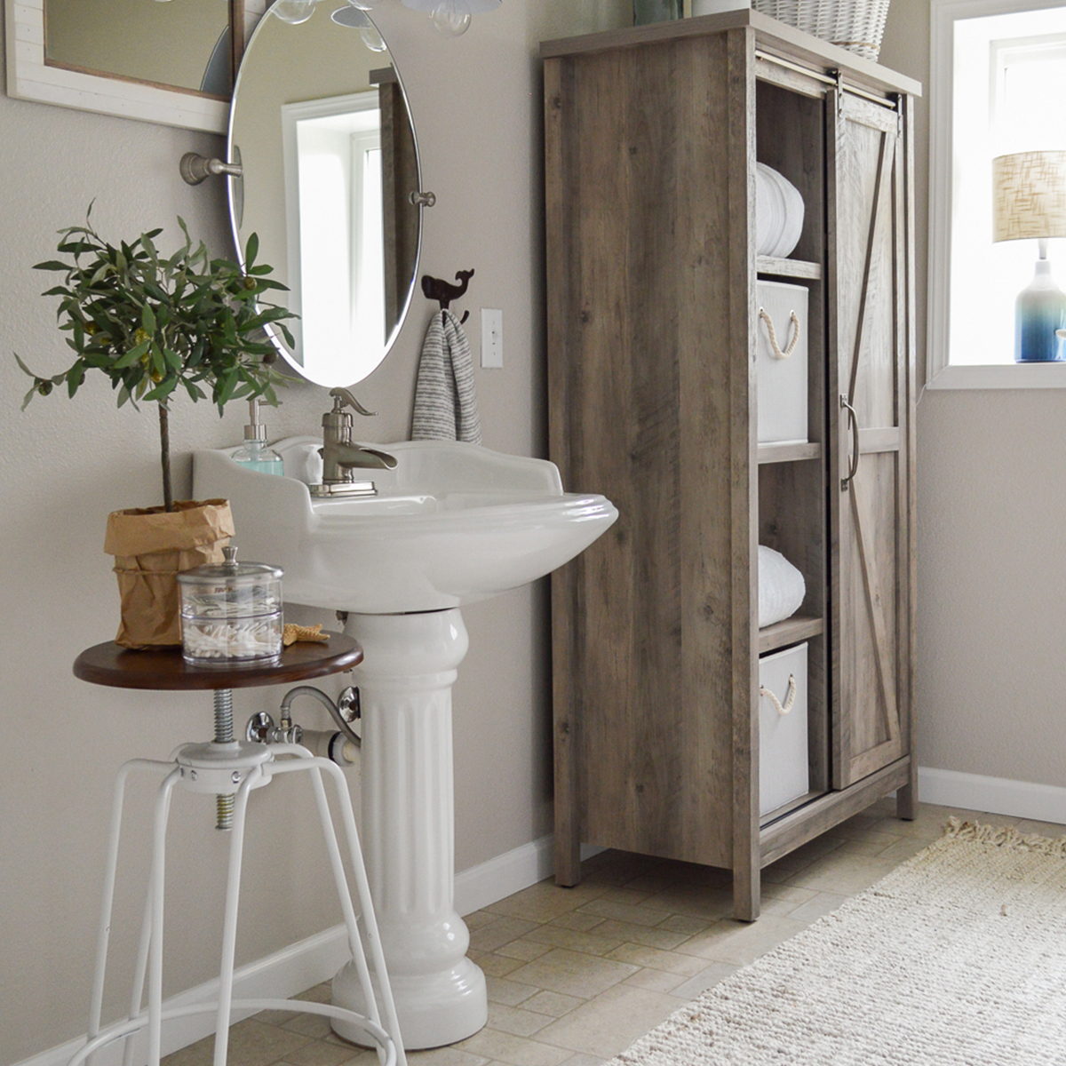Between the Modern Farmhouse Storage Cabinet, Collapsible Fabric Storage Cubes, and the Adjustable-Height Spin Stool, Shannon Fox of Fox Hollow Cottage creates the ideal farmhouse DIY bathroom makeover. photo