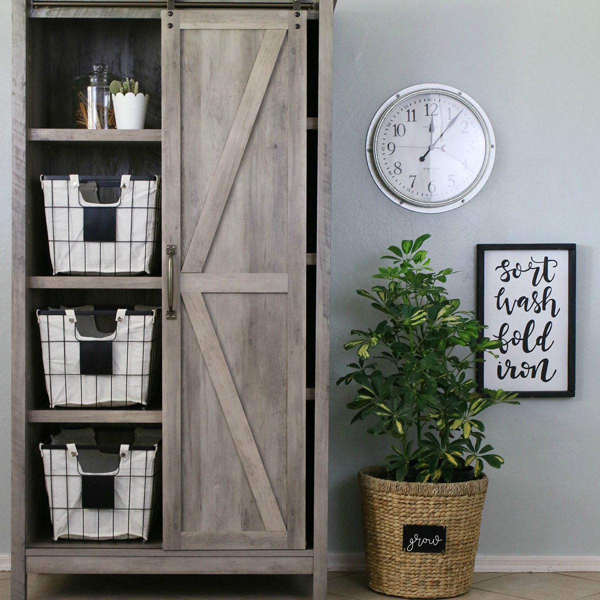 Incorporating a Round Hyacinth Twist Handle Basket and a Galvanized Wall Clock in her new-and-improved laundry room helps to add a touch of charm to the functional and stylish Modern Farmhouse Storage Cabinet. photo