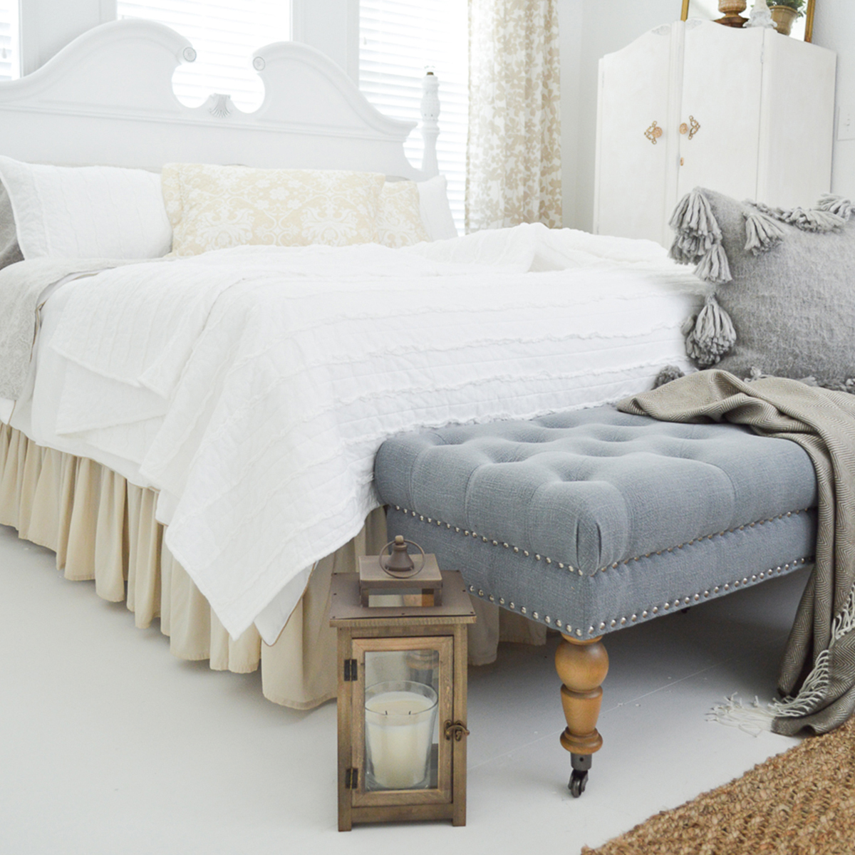 Create a farmhouse guest room with a comfy memory foam mattress, ruffle stripe quilt, farmhouse lantern, and woven fringe throw. photo