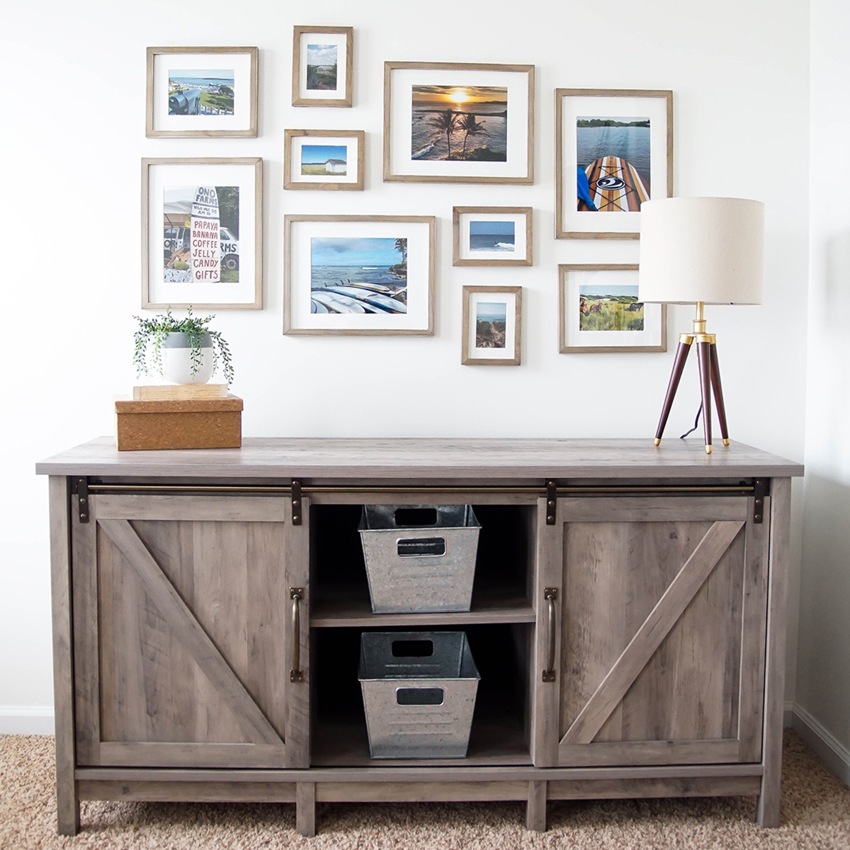 Modern farmhouse tv stand with a combination of solid wood picture frames hung above and stylish tripod table lamp. photo