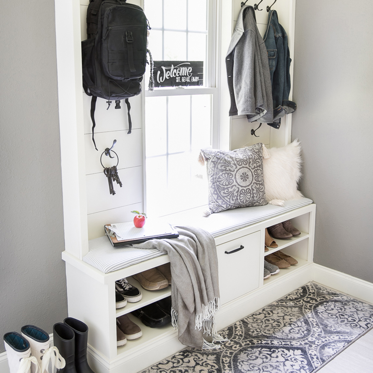 Turn your mudroom into an stylish alcove with a distressed area rug and soft woven fringe throw. photo