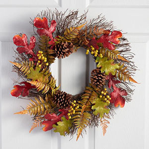 Fall wreath featuring leaves, branches, and pinecones. photo