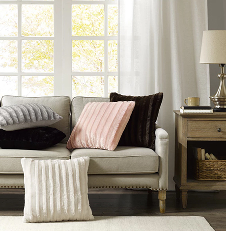 An assortment of faux-fur throw pillows placed on a neutral, beige couch. Throw pillows are in blush, cream, navy, and gray. photo