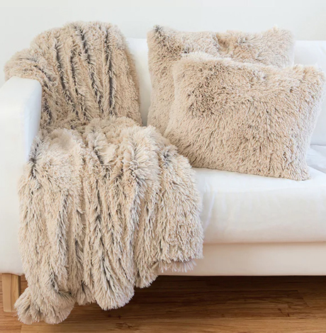 A neutral-colored, beige faux-fur blanket and pillow on top a white couch photo