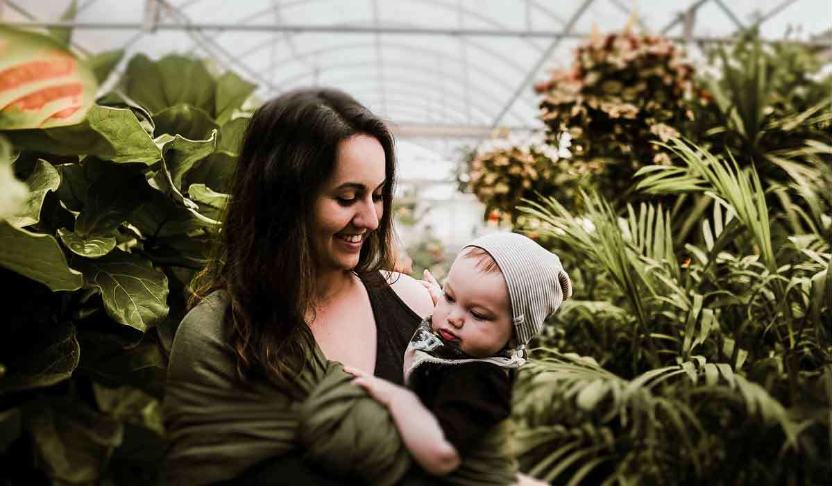 mom holding baby in a greenhouse with nursing bra on