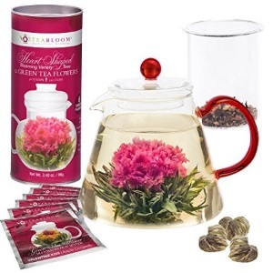 Clear teapot with blooming teas photo