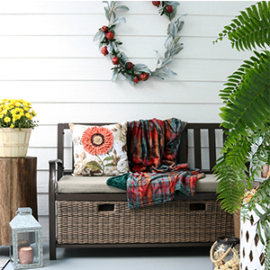 Cute farmhouse storage bench with coral sunflower pillow and plush velvet throw. photo