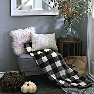 Cozy entryway with distressed area rug, tufted ottoman, and decorative pillow. photo