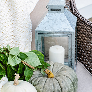 Beautiful back porch with galvanized lantern and chunky knit throw with a small table or chair can create the perfect fall nest. photo