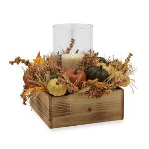 Hurricane glass in a wooden box surrounded by fall foilage and faux colored pumpkins photo