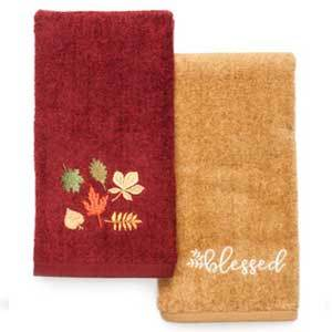 Two hand towels, one in red with leaves printed on it, one in yelow with the writing blessed on it photo