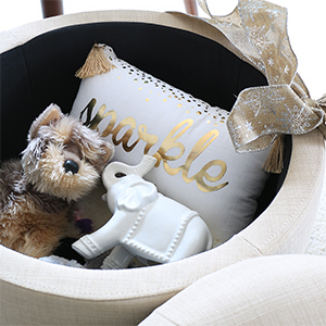 A white and gold throw pillow, white elephant ornament, and stuffed dog inside a tufted ottoman photo