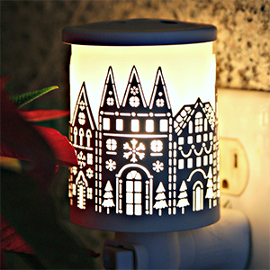 Black wax warmer that glows and shows a holiday building photo