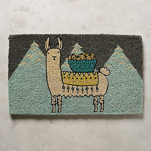 Doormat with charcoal gray background, light, sky-blue mountains on the bottom, and a llama character in front. photo
