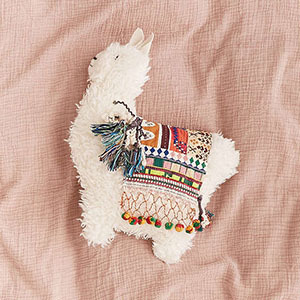 Faux-fur llama-shaped pillow with vibrant saddle over it photo