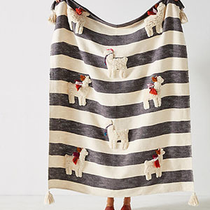 Striped off-white and charcoal gray throw blanket with small llamas dispersed around on it photo